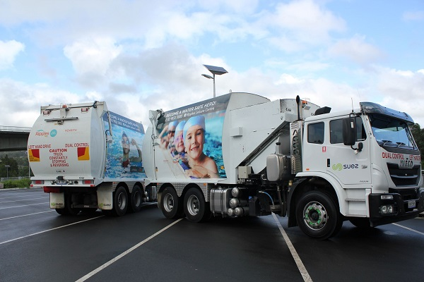 Two garbage trucks parked side by side displaying water safe messages