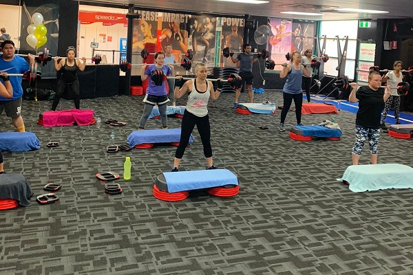 Class attendees perform an exercise at a group fitness class