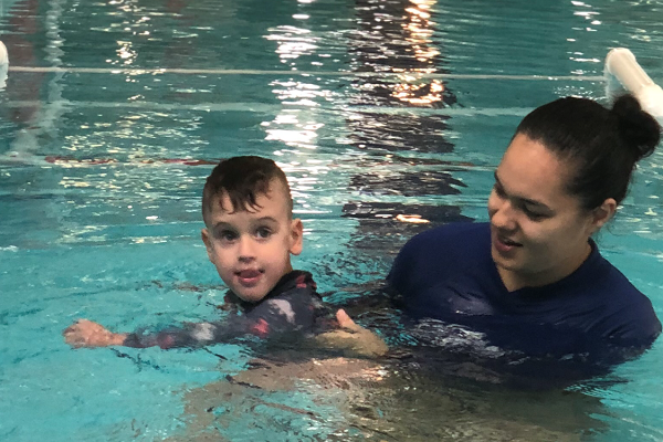 A female swim instructor assists a young boy learn to swim
