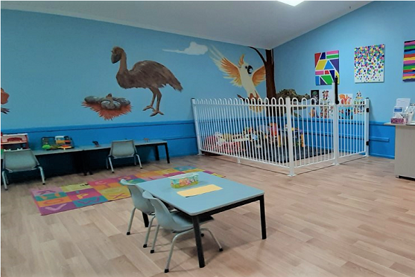 brightly painted room with childrens toys and tables in foreground
