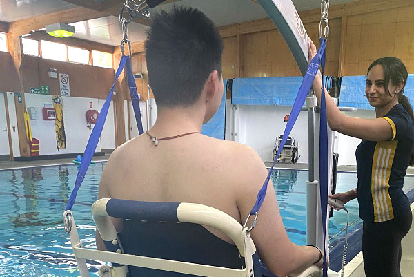 Ripples exercise physiologist assisting a male patient into the water with the wheelchair hoist